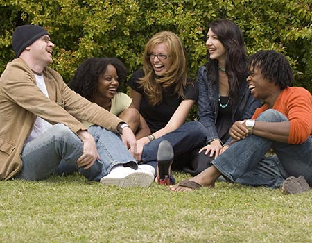 five college students sitting on the grass and smiling