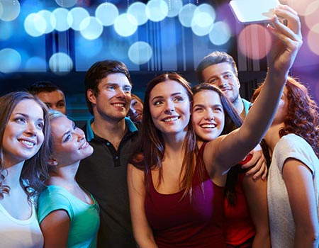many teenagers at a party taking a selfie