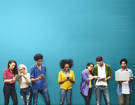 seven young people standing looking at phones, tablets, and computers against a greenish-blue background